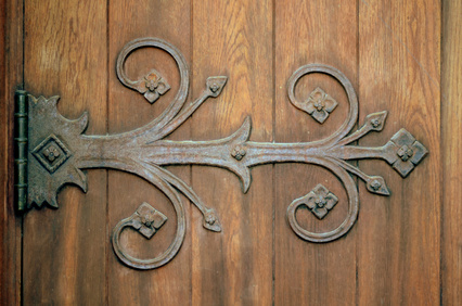 Ornamental iron hinge on old wooden door